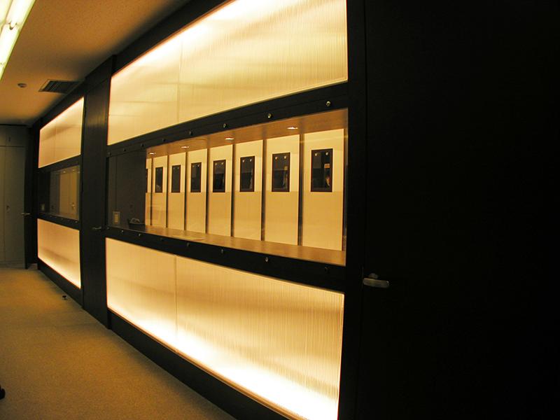 オフィス移転工事 福岡県福岡市中央区大名の事例事務室から照明壁を通して展示照明壁を眺める
