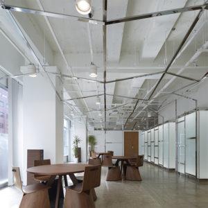 オフィスデザイン・オフィス移転工事 東京都渋谷区神宮前のマスコミ・クリエーター人材派遣会社のオフィス移転工事の事例です。原宿というトレンドにとって特別な地域の街の景色を入り込ませている左側の既存サッシがあります。サッシフレームと新設するホール室内の一体感を持たせるため、ピッチをサッシにそろえながら、天井フレームのフラクタルなステンレス鏡面の雲(クラウド)を作成しています。天井のフラクタクルなステンレス鏡面フレームが遮音壁兼内照壁まで降りてきてホール室内全体を覆うデザインとしています。ホール窓側にスクリーンを下ろして、セミナーや講習会を行えるレイアウトとしています。そのため、映像・音響設備も備えています。木製の親子扉の奥が事務室になります。透明のチェアは相合家具のSMART・Sです。