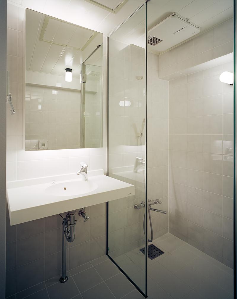シャワールームと洗面・トイレの3IN1 手前にはトイレがあります。FRP防水の3IN1で強化ガラスフレームレス間仕切りとして設計しています。 床暖房方式ではなく、床タイルはTOTOサーモタイルとして足さわりのヒヤッと感を軽減するようにしています。また、3乾王という換気・暖房・乾燥機能のある浴室親子換気扇を設けています。また親子機能が付いていまして、浴室部の換気以外に換気ダクトで他室を同時に換気する機能があります。 3IN1とはバス・トイレ・洗面が一つの部屋になっていることで広く見せる効果があります。