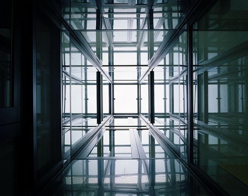 光庭を3層先の天開口まで見上げる この住宅で特徴的なのは3階メゾネットつまり3階建てということですが、南面しか窓開口を取る事が、マンション共用部プラン上、構造上できない制約がありました。 その中でも通風を確保して、さらに北側の窓に面していない階段室や北側居室を自然光で照らしたいと検討しました。その中で南面開口と光庭開口で3層で重力換気が起こるよう計画しました。 また、単なる重力換気だけでなく光庭は煙突効果も望めるため大きな換気効果が見込めます。 省エネルギー環境建築の要素を盛り込んだ設計手法としています。 重力換気について 重力換気とは、室内外の温度差により空気に重量差が生じて発生する動力を用いないで自然条件を利用した換気方法をいいます。 煙突効果について 煙突効果とは、煙突の中の暖かい(軽い)空気の下に、冷たい(重い)空気が潜り込み、暖かい空気を押し上げる効果のことです。この押し上げる力を通気力、ドラフトと呼びます。 鏡面ステンレスが光を遠くまで届ける パッシブ設計のなかで光ダクトという手法があります。 光ダクトとは内部が鏡面になっているダクトに自然光を取り込み、反射を利用して光を搬送し、照明用の光源として利用するものです。 この光庭は鏡面ステンレス貼り仕上げとサッシガラス面で構成されています。 片岡直樹建築設備設計一級建築士事務所では、見た目だけのデザインではなく建築設計者として、居心地の良い空間を作ることが大切だと考えております。 そのために、仕上の美しさだけでなく、空気環境や光環境のデザインコントロールに注力しています。