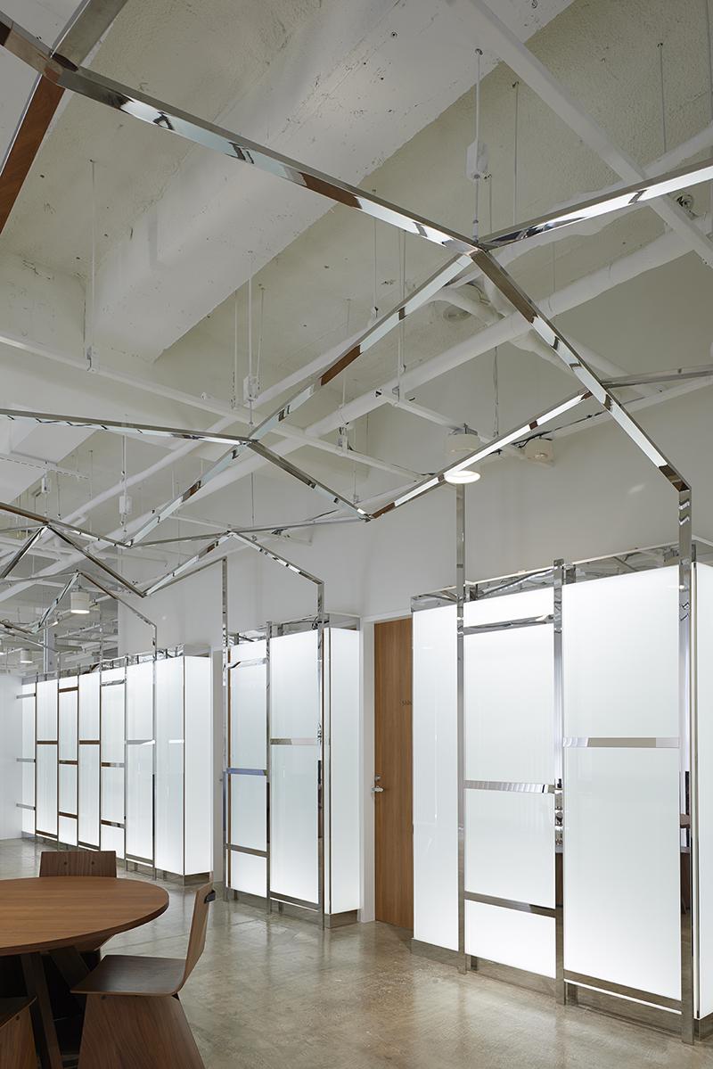 ホールから面談室側の眺め 鏡面ステンレスのフレームが内照壁のガラスのシール分割目地を隠しています。新築工事と違い、テナント内装工事はエレベータカゴの大きさや階段などの搬入限界があるため部材の長さや大きさに制限が大きくあり、今回は特に条件が厳しくガラスが分割搬入となっていました。