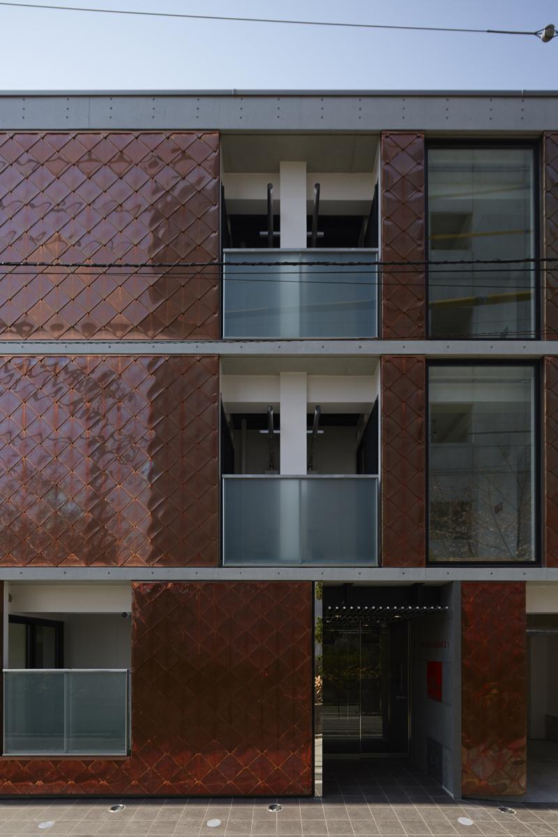 道路側見返しのファサードの眺め 都市計画法の緑地なので鉄筋コンクリート造は建築することが出来ません。 敷地は台形の変形敷地です。収益率を最大にするため建蔽率いっぱいに建物を計画しています。 建蔽率いっぱいで、緑化計画必要面積とワンルームマンション条例により最低居室面積が決められて、その上に地区計画で建物配置に規制がかかるという針の穴を通すような厳しいプランニング検討作業になっています。 普通、共同住宅では容積率とレンタブル比がプランを決定付ける上で重要になりますが、本敷地条件は、都市計画区域なので3階までしか建てられないため、容積率より先に建蔽率が厳しくなります。 ブレースを無くして、そのスペース分を貸し室面積に振り替えられ、プランの自由度が得られる鉄骨造純ラーメン構造としています。 型枠の転用回数を多くすることでコスト削減のメリットがあるため、既製プランとする必要性があるプレキャストコンクリート造や、ある程度偏心のない平面計画となるように、長方形のきれいなプランが必要なXYブレース構面のある工法は採用できません。 きれいな矩形プランであればX・Y方向に壁面ブレースを取った、プレース耐力壁ラーメン構造として少しでも柱を細くするか、もっと軽量化すれば柱なしのブレース耐力壁鉄骨構造も可能です。 しかし、柱なしブレース耐力壁鉄骨構造にするためには、マンションとして重要な要素である防音・遮音性能も犠牲にして、軽量化を最大までする必要があります。 外壁をサイディングで下地をケイカル板として耐火性能を確保するなど鉄骨アパートの仕様にどんどん近づいていきます。ここがとても難しい選択です。 建築基準法では共同住宅として同じ定義ですが、マンションとアパートではオーナー様・入居様の見方はまったく違います。 鉄骨アパートの仕様は、お施主様が望む建物のグレードではないとのご指導から採用しませんでした。 重量鉄骨造3階建てで、マンションのような価値のある建物とのご要望を頂いておりました。 そのため、耐火建築物重量鉄骨造でありながら、上下階の防音・遮音性能を鉄筋コンクリート造マンションと同じ仕様として、コンクリートスラブ165mm厚を打設して鉄骨梁とスタットボルトで床面と梁を定着させる工法で設計しています。 通常、鉄骨造ALC建築であれば床は山形のデッキスラブとして山部分で70程度、谷部分で120程度のコンクリートが打設される工法か、もっとグレードを下げるとALC床となります。 デッキスラブやALC床では、防音・遮音性に必要な重量(正確には面密度ですが・・・)を稼げないため、鉄筋コンクリート造と同じ防音・遮音性能を望めません。 デッキスラブで鉄筋コンクリート造150mm厚スラブ並みの防音・遮音性能を確保するためには、山上で150厚さのコンクリートを打つのが簡単ですが、それですと、ただコンクリートの重みが増えるだけで防音・遮音性は上がっても、単なる重量増となるだけで耐震性能としては悪くなります。 ニュートンの運動方程式のF(地震力)=m(建物重量)×a(地震の加速度)です。m(重量)が大きくなれば建物が受けるF(地震力)が大きくなります。 また構造計算の側面でとらえますと、デッキスラブはデッキの谷部分を梁に溶接して床スラブと梁が一体となる剛床仮定が成り立ちます。しかし、折り曲げた構造なのでX・Y方向では実際にはスラブ厚さが違うので剛床の剛性も違ってくるはずです。 コンクリートスラブ165mm厚を打設して鉄骨梁とスタットボルトで定着させる工法では、より強い剛床が成り立ちます。 剛床仮定とは構造計算において、各層ごとの変位が一定であるという条件で構造計算できることをいいます。 ラーメン構造とは柱・梁剛接合のことです。柱と梁が水平地震力を受けても接合部は変形せず直角を保とうとします。その反対がピン接合などです。 柱が何本か立っている建物の床の重さや重心に偏りがあれば一番偏ったところの柱に大きな変位が起こります。しかし、この剛床仮定が成り立つということは、すべての柱に均等に水平地震力が作用するということになるので、ある程度の範囲内の不整形な建物でも、均等に地震力が作用するのでバランスが良くなるということがいえます。 今回の敷地は不整形な建物となるため、この剛床が強く成り立つこの工法はとても有効だと考えています。 そこで、デザイン的にも床がコンクリートであることをを表現するためALCパネルの間にコンクリート床の小口が165mmの厚みで見えるデザインとしました。 防音・遮音性と剛床仮定そしてデザインの3方で生かしたコンクリート床としています。