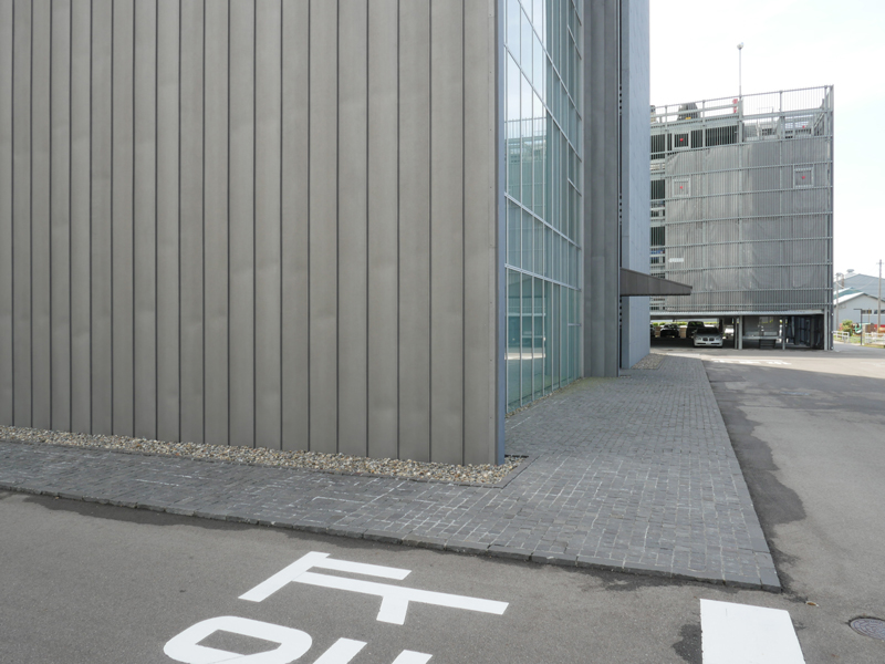 片岡直樹の建もの探訪|ブルボン本社ビルガラスカーテンウォールと金属板外壁の取り合い部から裏手の駐車場側の眺めです。