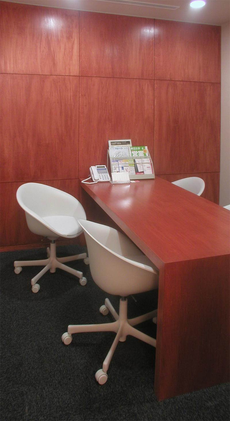 事務所引越移転内装工事|東京都港区南青山でのオフィスデザイン事例 面談室2 面談室は壁面の一部と机を同素材として共通性を持たせ壁パネル目地間隔と机幅が合うように設計して壁と机の一体感を演出し小さな部屋でも広がりが出るように設計しています。 イスはそれぞれの面談室でかえて違う雰囲気が楽しめるように什器選定をおこないました。