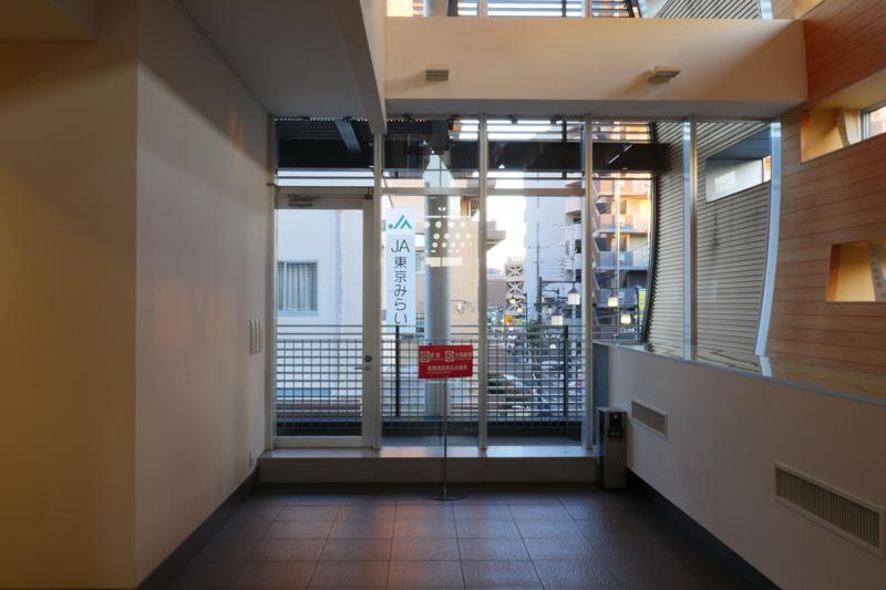 2階階段奥妻面のバルコニー出口|片岡直樹の建もの探訪|清瀬けやきホール 新築であれば床レベルと開口部下端高さをフラットそろえたいところですが、開口部立ち上がりが床レベルから露出しています。右手は空調のダクトが通るボックス部分でしょうか。唐突に曲面壁から飛び出ています。改修設計ではどうしても既存躯体のデザインが制約されるので、どうしてもコントロールできない部分を覆い隠さざるをえないのだと思います。新築のようにデザインしようとすると、とても苦しく悩んでしまうような大変な設計だと思いました。どこかで改修設計だと割り切る部分が必要になるのだと思います。