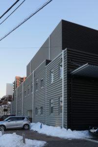 バックヤード側外壁ディテール|片岡直樹の建もの探訪|清瀬けやきホール 折半の谷部分と既存外壁との間に面戸部分でクリアランスがありません。外壁に縦胴縁下地なしで直接折半を止める化粧ビスを打っているのでしょうか。既存外壁が層間変位のない鉄筋コンクリートなので良いかと思いますが、既存外壁の不陸処理などこれだけ長い面を通そうとすると思った以上にモルタルを塗り付けることになるように思います。 私はマンションの大規模修繕で外装デザインで面一おさまりを行い、既存躯体の不陸の多さに悩んだことがあります。