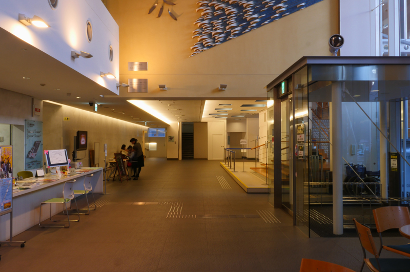 エントランスホール|片岡直樹の建もの探訪|清瀬けやきホール 増築部分と既存部分の間がホールとなっています。階段のデザインがカッコいいのですが、段が不規則で危ない表現に思いました。
