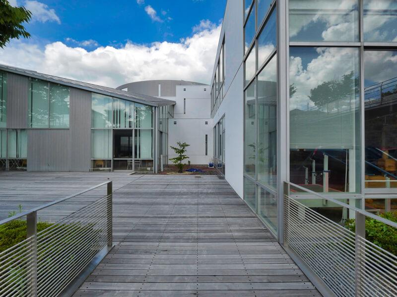 木デッキの中庭 住宅/ビル/マンションのデザイン建築設計事務所をしている片岡直樹が向学のために名建築を訪ねるシリーズです。福島県郡山市にあります渡部和生先生による設計の福島県立郡山養護学校を見学してきました。職員の方の許可を頂き外観と内部撮影をさせて頂きました。新建築 新建築 2001年7月号に発表された作品です。国内で最も権威のある建築の賞である日本建築学会賞・作品賞を2004年に受賞されています。